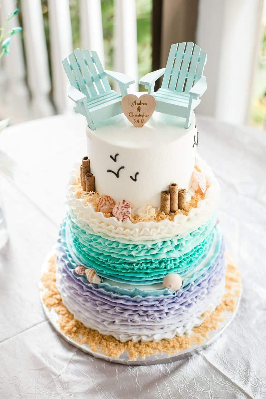 Our DJ Rocks at Paradise Cove beach themed wedding with teal uplighting wedding cake