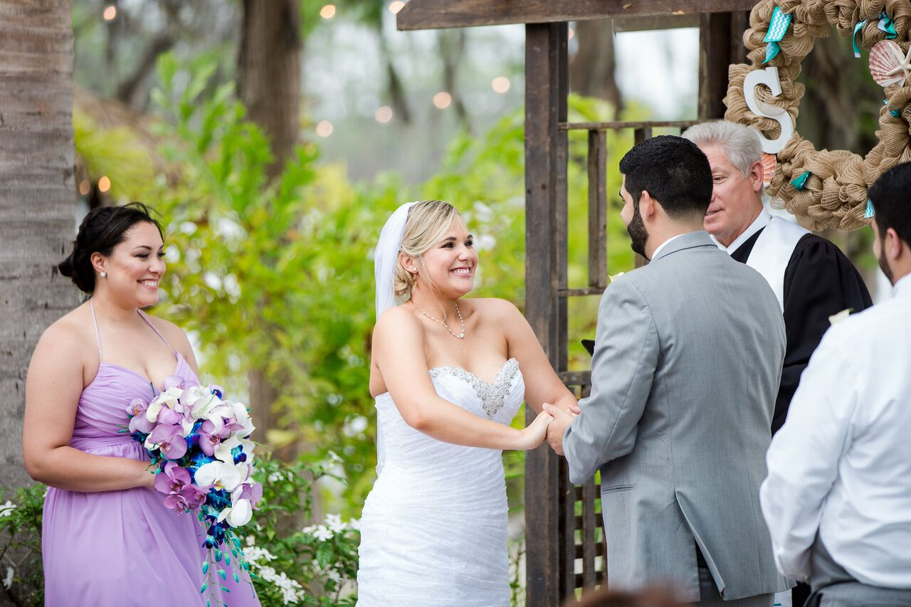 Our DJ Rocks at Paradise Cove beach themed wedding with teal uplighting bride and groom at ceremony