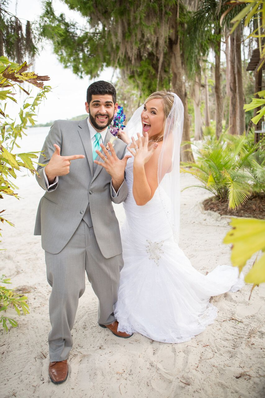 Our DJ Rocks at Paradise Cove beach themed wedding with teal uplighting bride and groom showing off rings