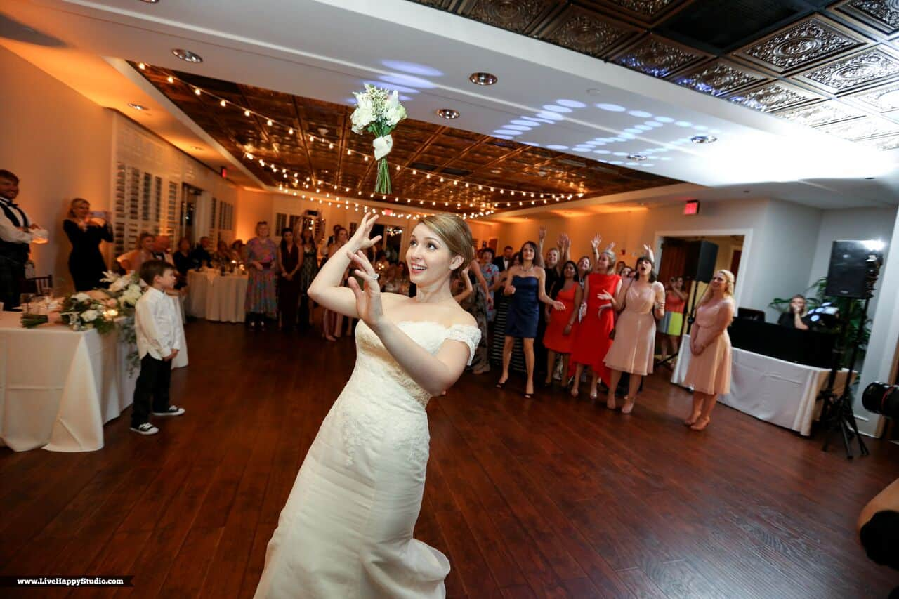 emale wedding dj at scottish inspired wedding at The Golden Bear Club wedding bouquet toss with amber uplighting