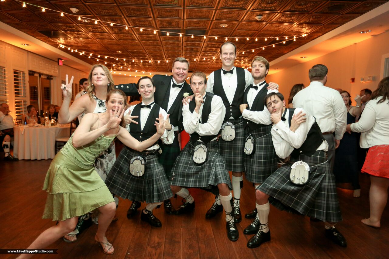 emale wedding dj at scottish inspired wedding at The Golden Bear Club wedding guests posing in kilts with amber uplighting in background