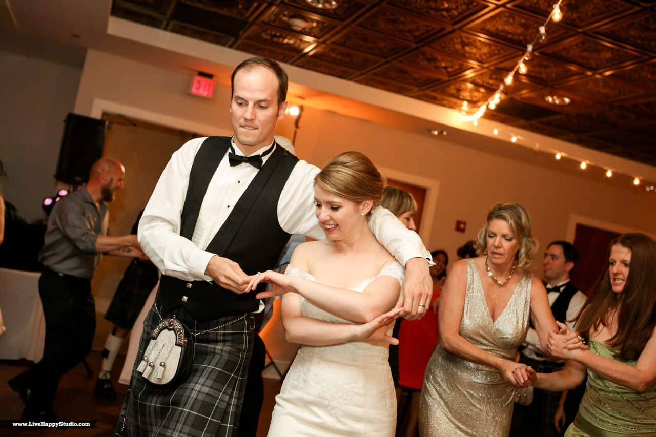 emale wedding dj at scottish inspired wedding at The Golden Bear Club wedding bride and groom dancing with amber uplighting in background