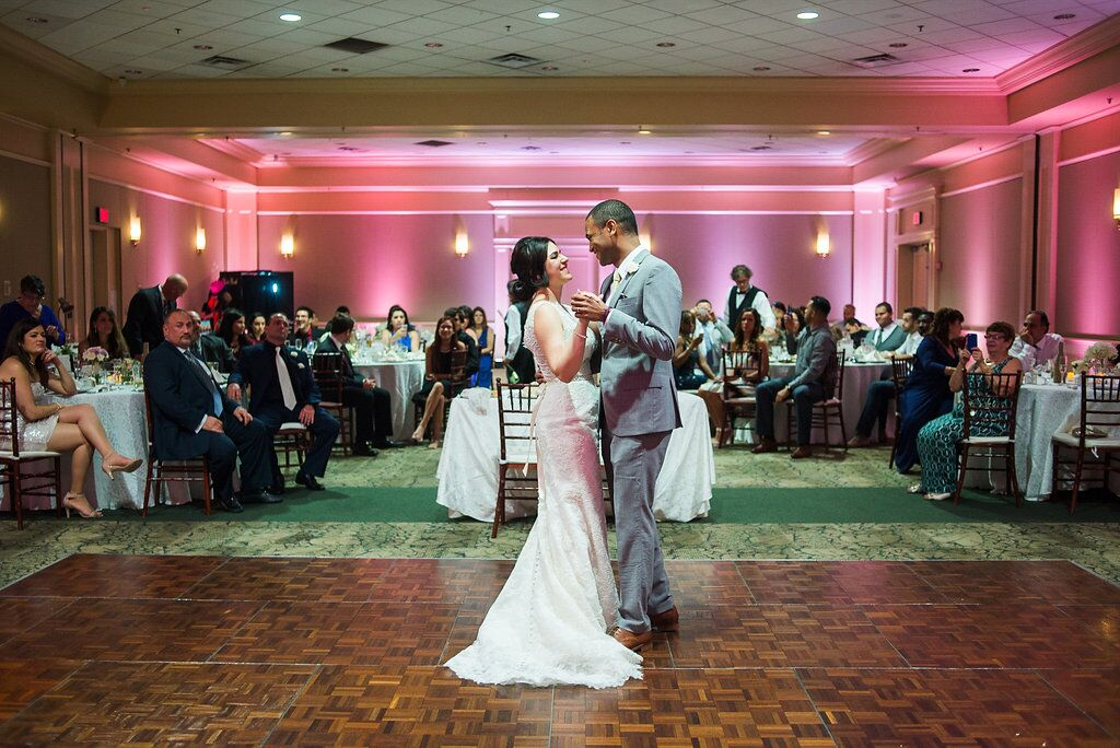 bride and groom first dance at leu gardens wedding with pink uplighting and dj in orlando