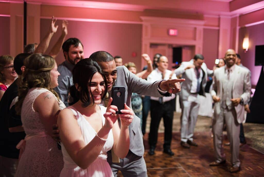 guests dance at  leu gardens wedding with pink uplighting and dj in orlando