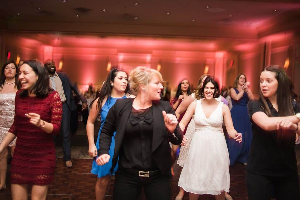 dj in orlando dancing with guests at leu gardens wedding with pink uplighting and