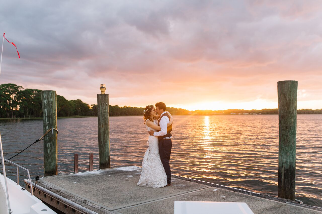 mission inn wedding with amber uplighting bride and groom posing by water at sunset
