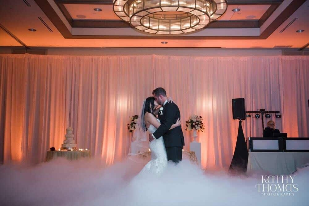 couple dancing on a cloud at Alfond Inn wedding kissing with amber uplighting and Our DJ Rocks