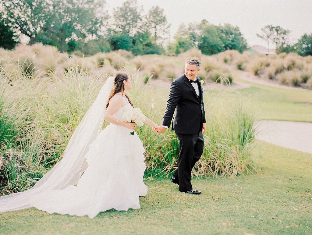 Villas of Grand Cypress Wedding with blush pink uplighting bride and groom holding hands