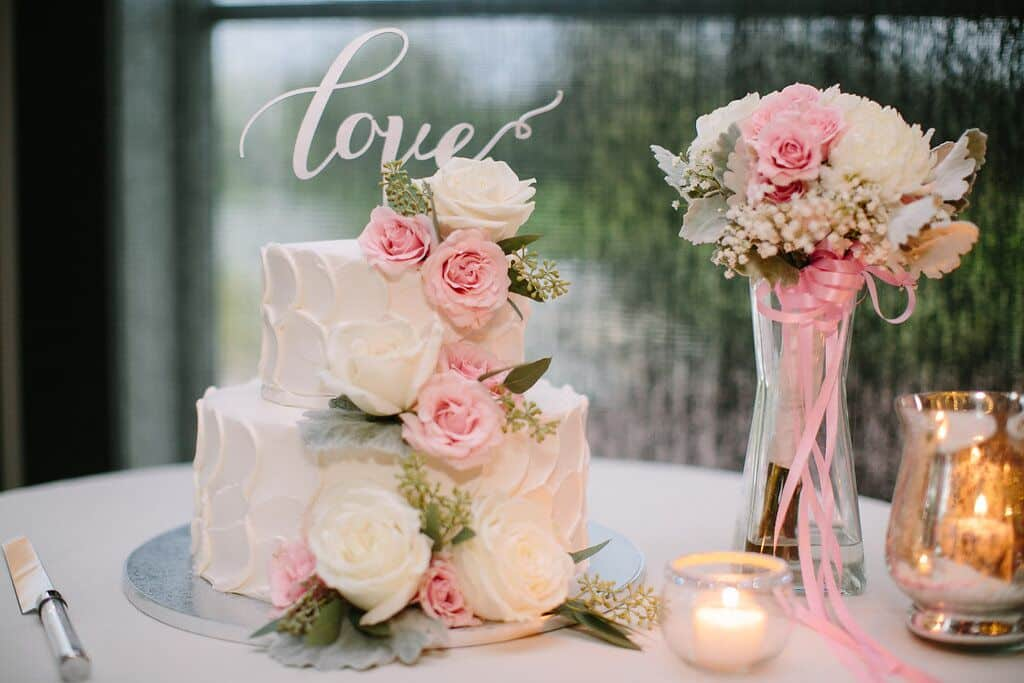 Our DJ Rocks at wedding at Noah's Event Venue white cake with white and pink flowers