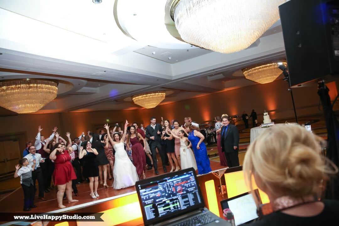 DJ behind table overlooking dancing guests