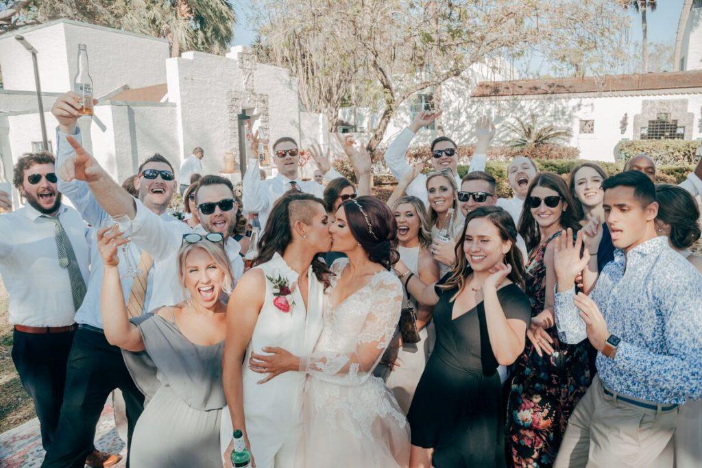 brides sharing kiss at wedding guests cheer
