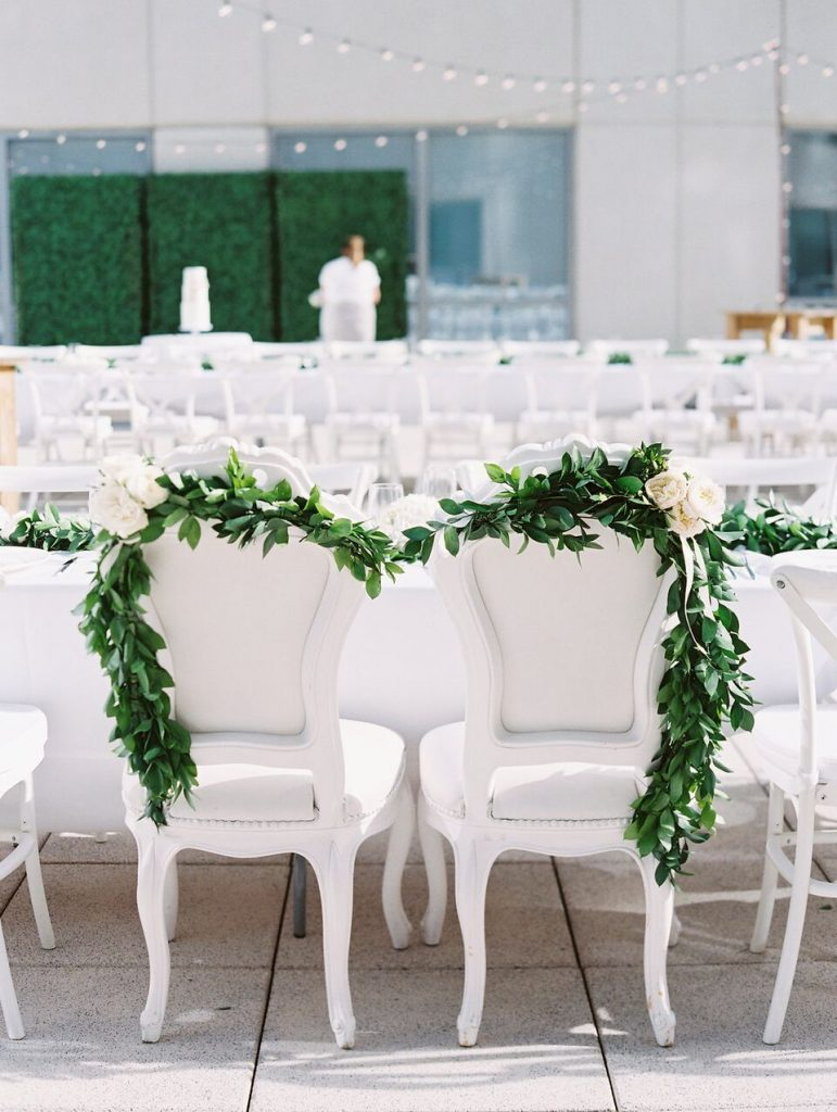 elegant white wedding reception chairs draped with greenery