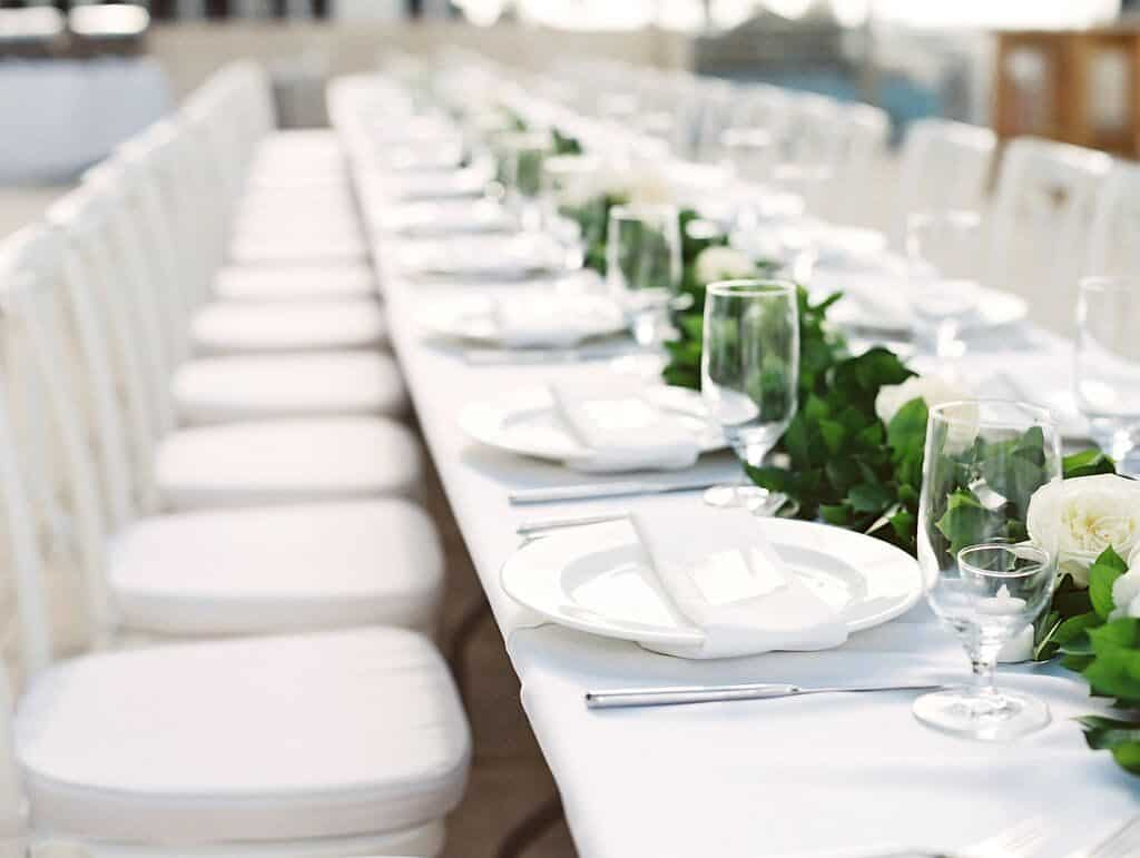 beautiful white table setting with simple greenery runner