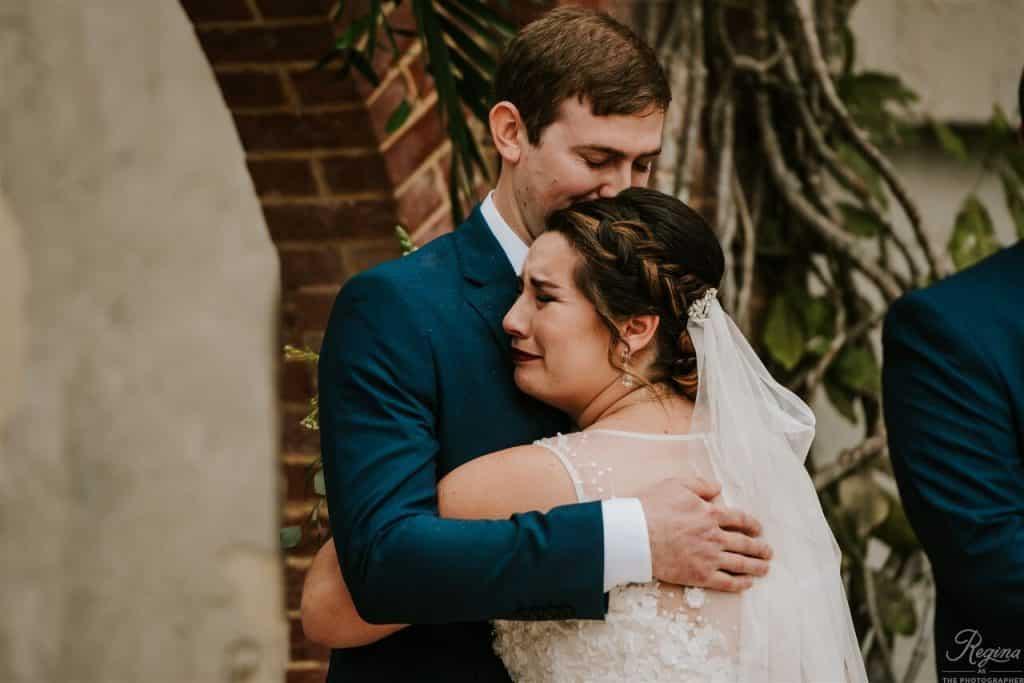 teary-eyed bride hugs groom