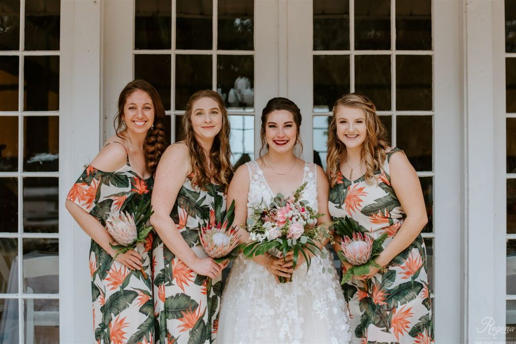 Bride with bridesmaids in tropical floral dresses