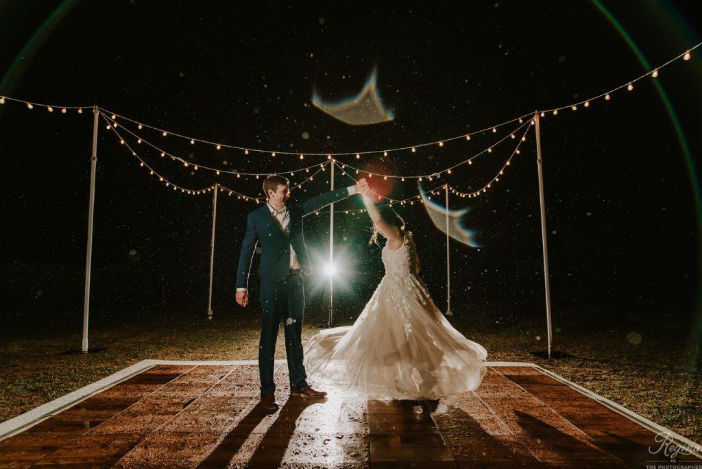 Groom spins bride on outdoor dance floor with mood lighting