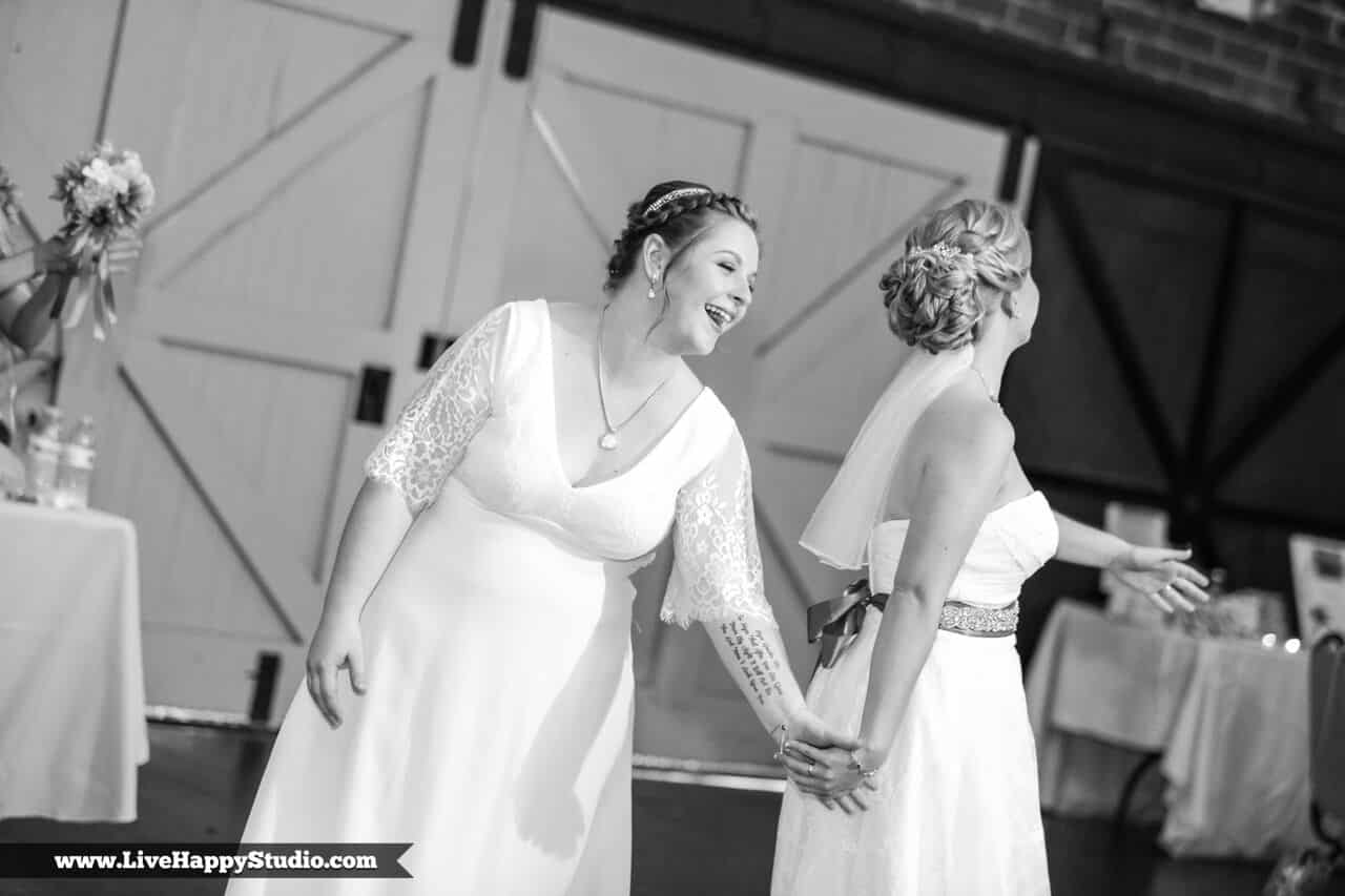 Brides holding hands on dance floor