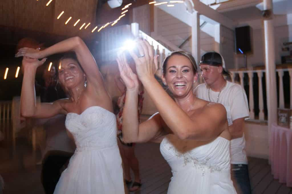 Two smiling brides on dance floor