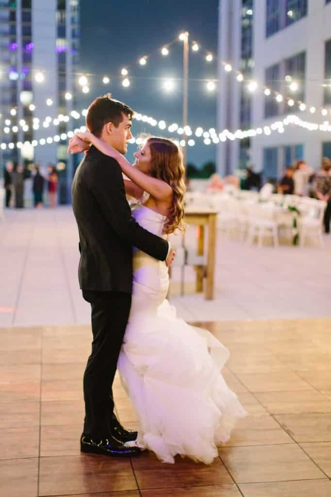 bride and groom share intimate dance on rooftop underneath market lighting