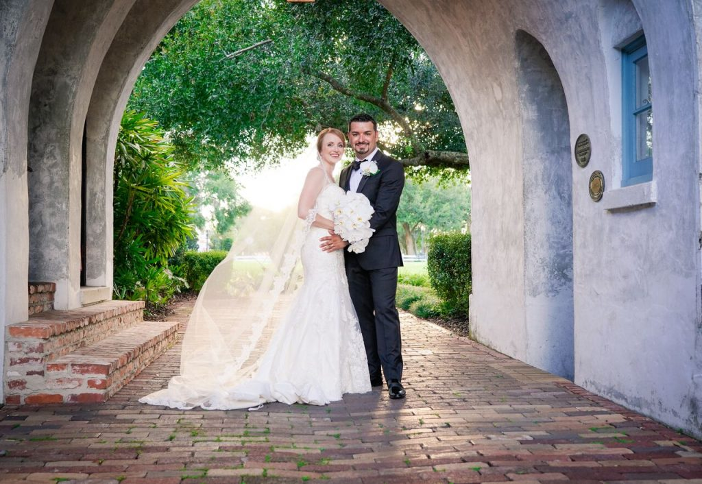 bride and groom under arch on brick walkway