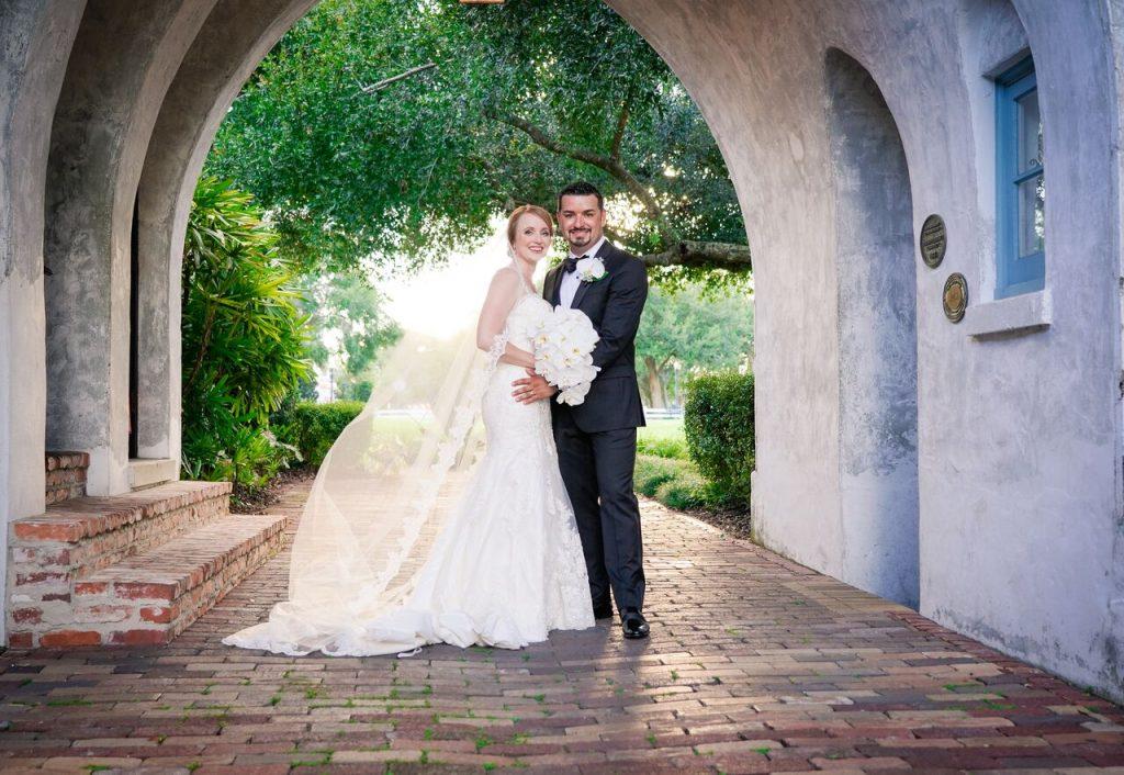 bride and groom under arch on brick walkway
