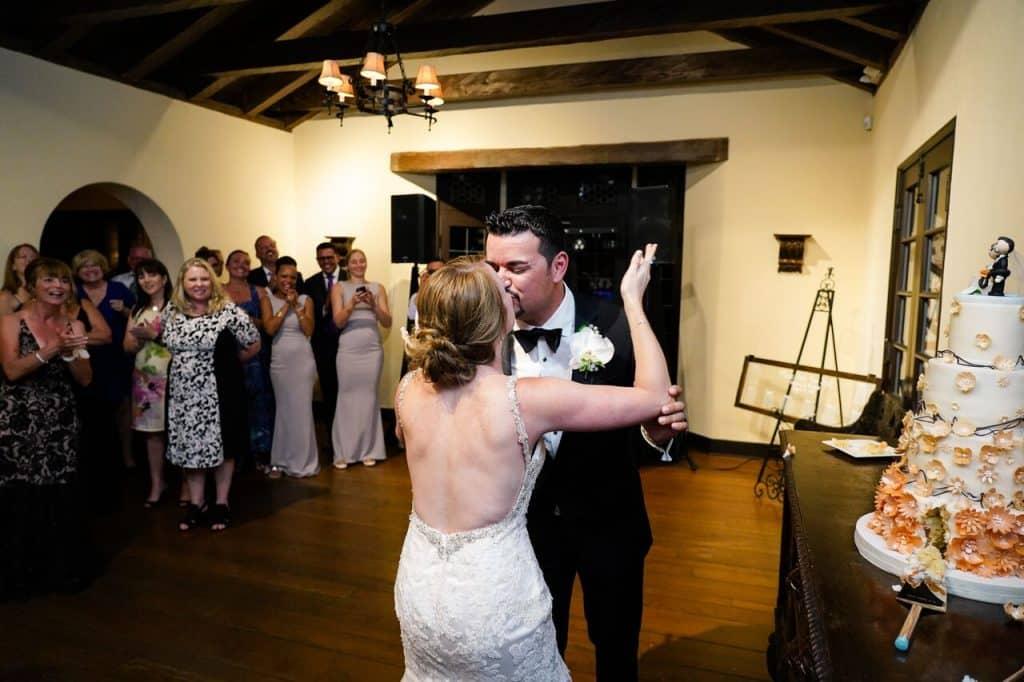 newlyweds kissing next to wedding cake