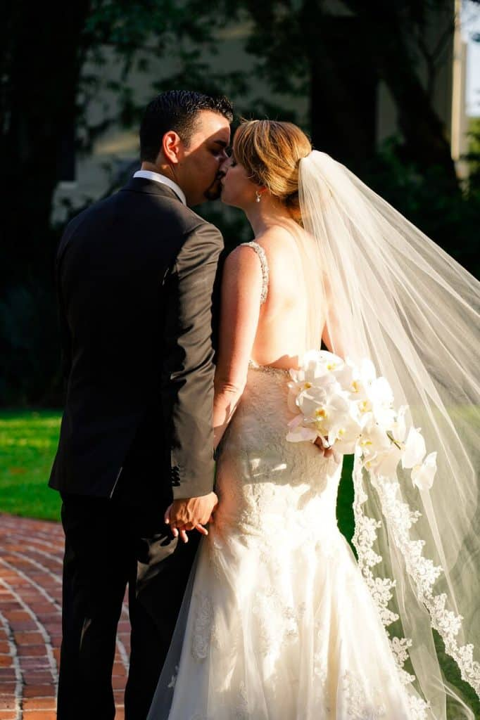 bride and groom holding hands and kissing