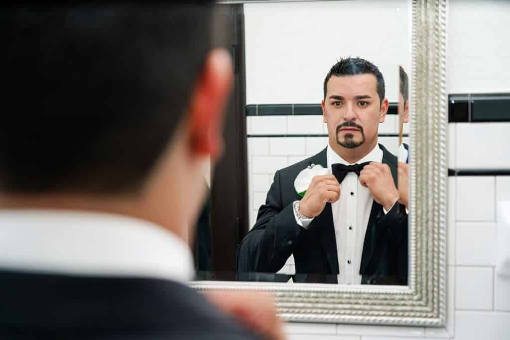 groom tying bow tie in the mirror