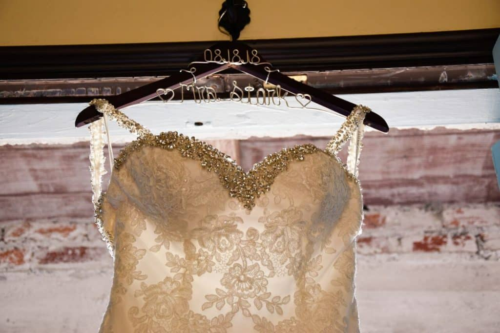 wedding dress hung up in front of window