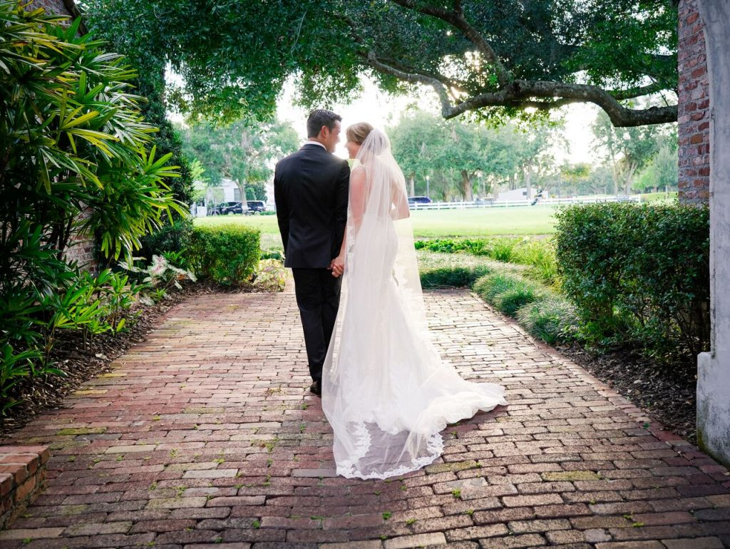 bride and groom walking away on brick path