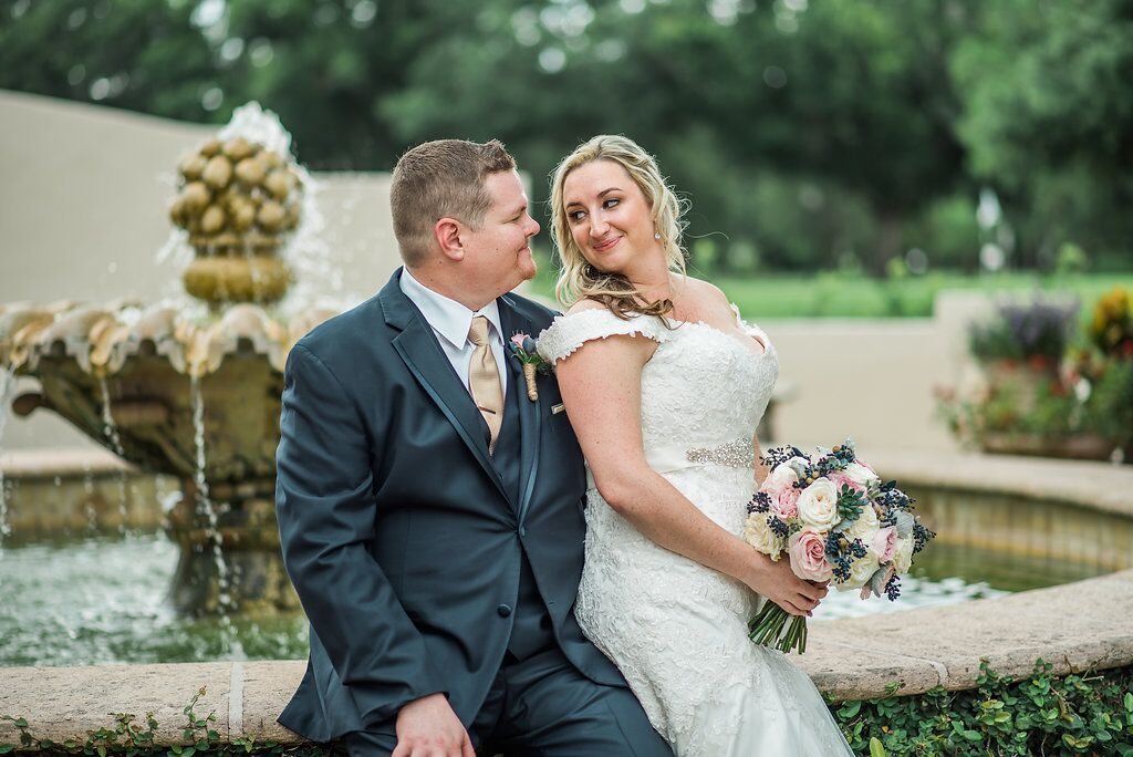 bride and groom posing on edge of Winter Park fountain