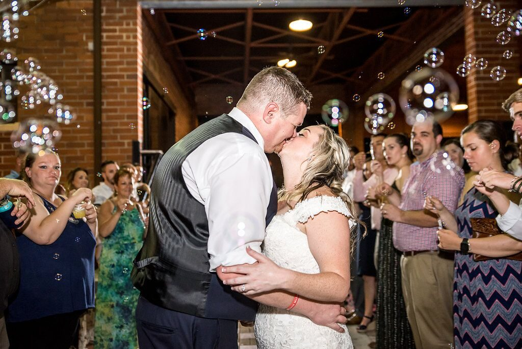 bride and groom kissing among cascade of bubbles