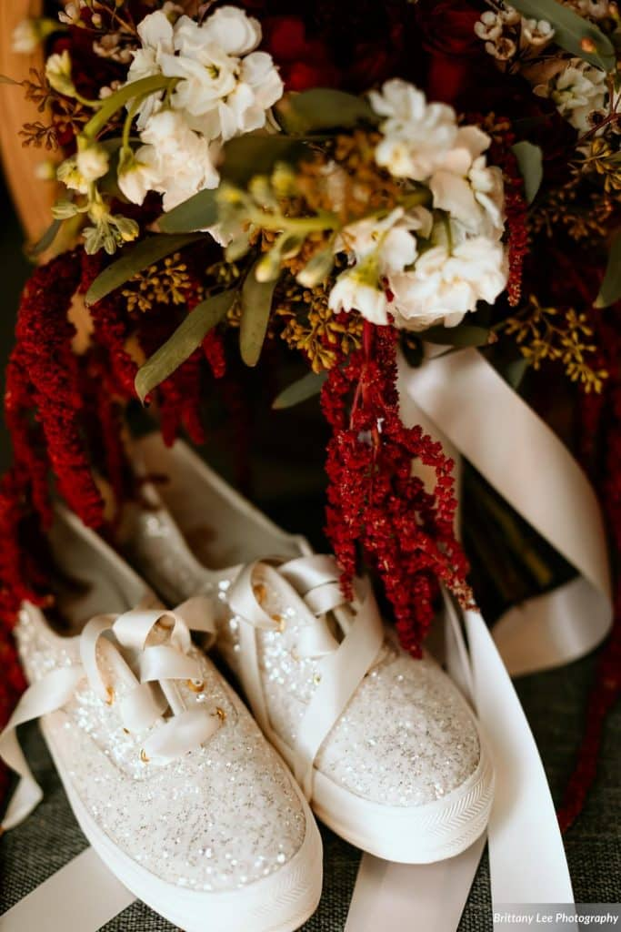 sparkly bridal sneakers next to bouquet