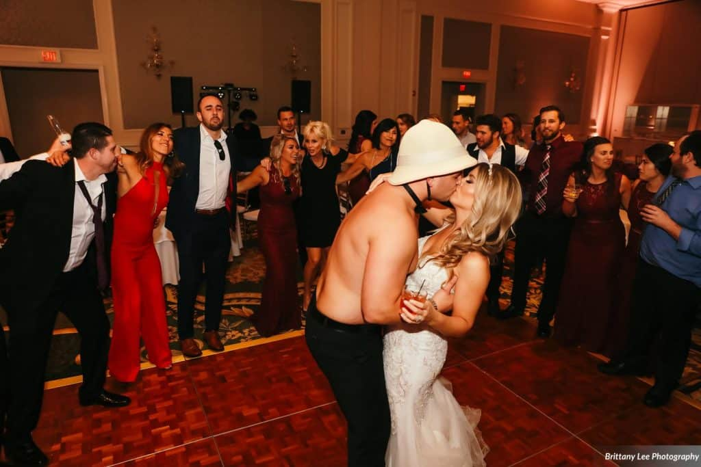 shirtless groom in safari hat kisses bride on dance floor