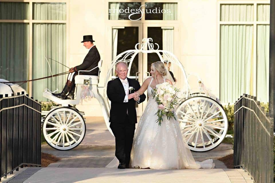 bride and father walking away from pumpkin carriage