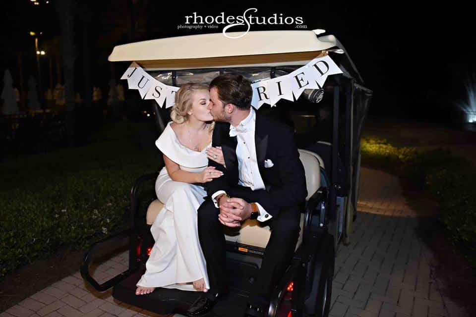 bride and groom kissing on back of golf cart