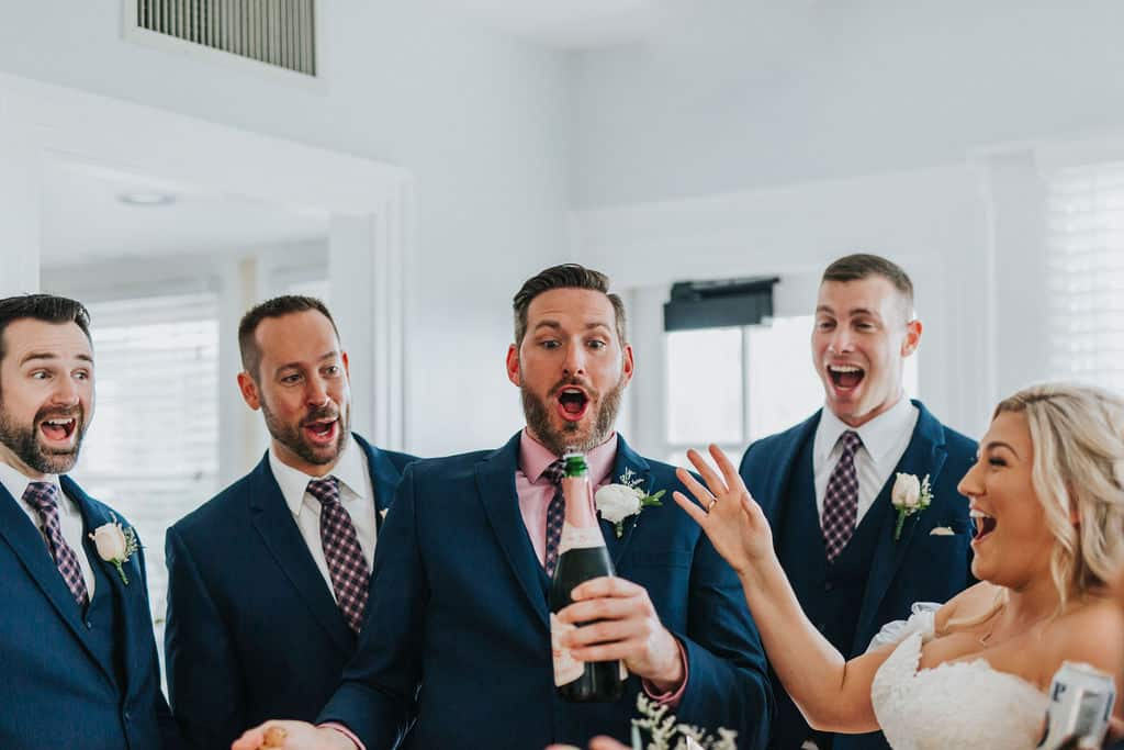 groom popping open a bottle of champagne with groomsmen