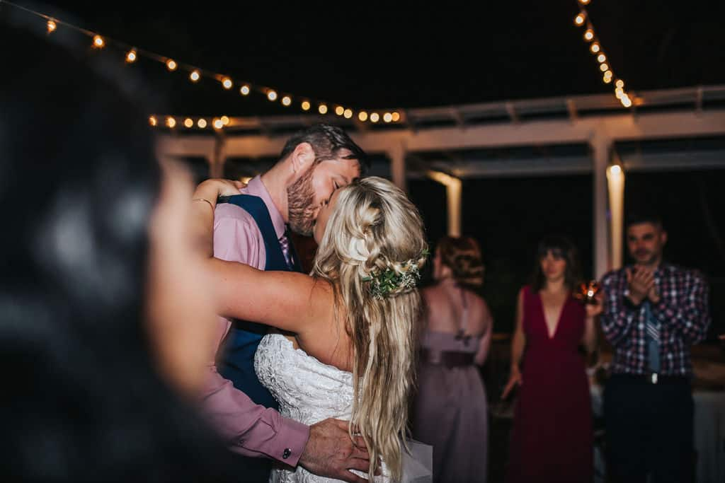 Albina and Scott kissing on the dance floor of their wedding.