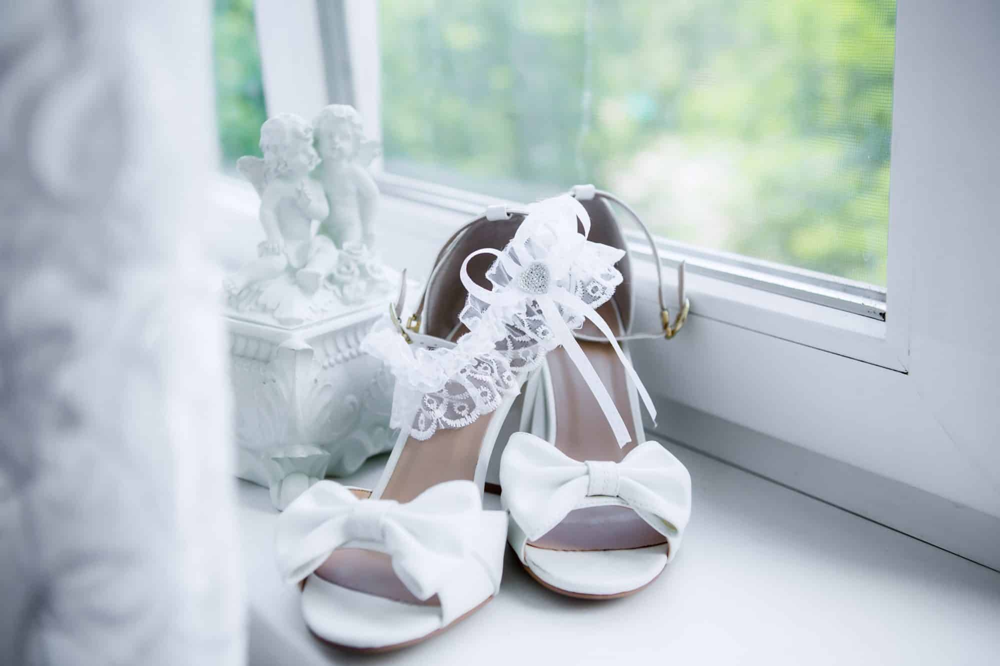 white heels and bridal garter next to window