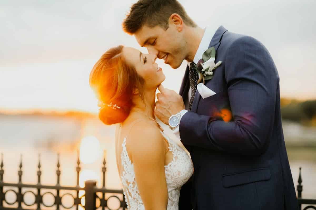 bride and groom kissing with sunset behind them