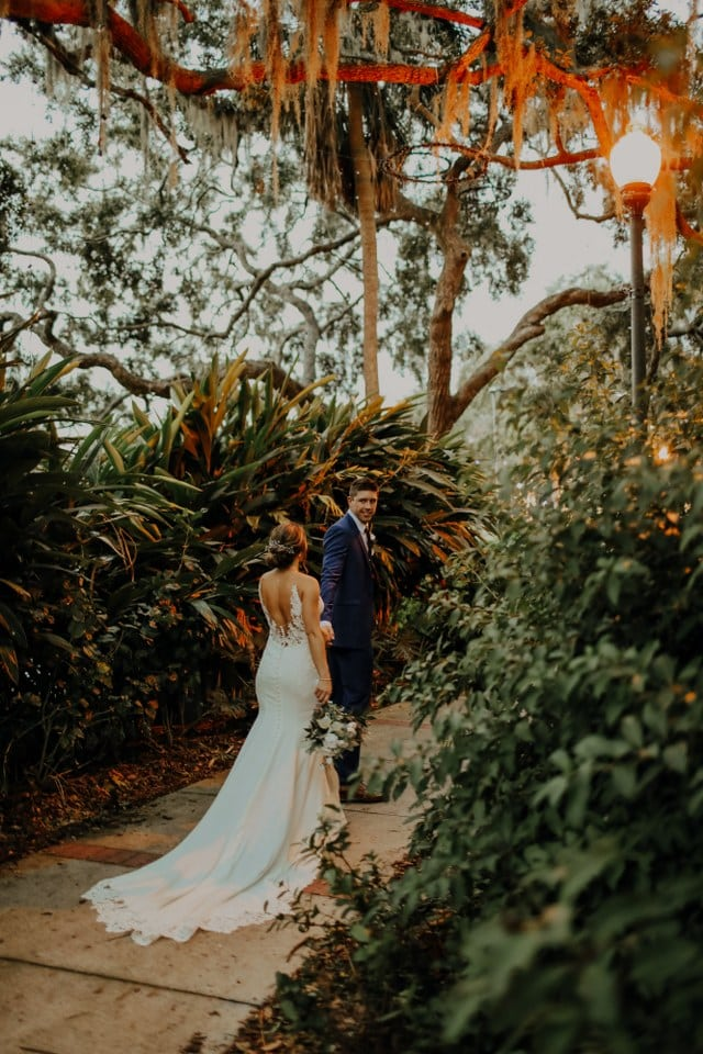 groom leading bride through lush garden setting