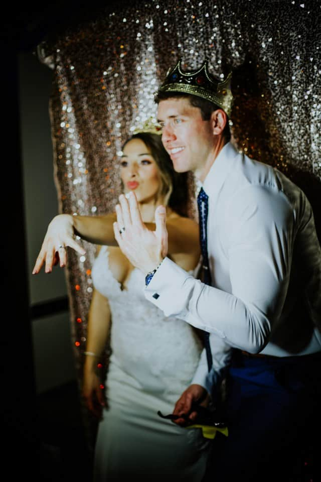 bride and groom showing off rings in photo booth