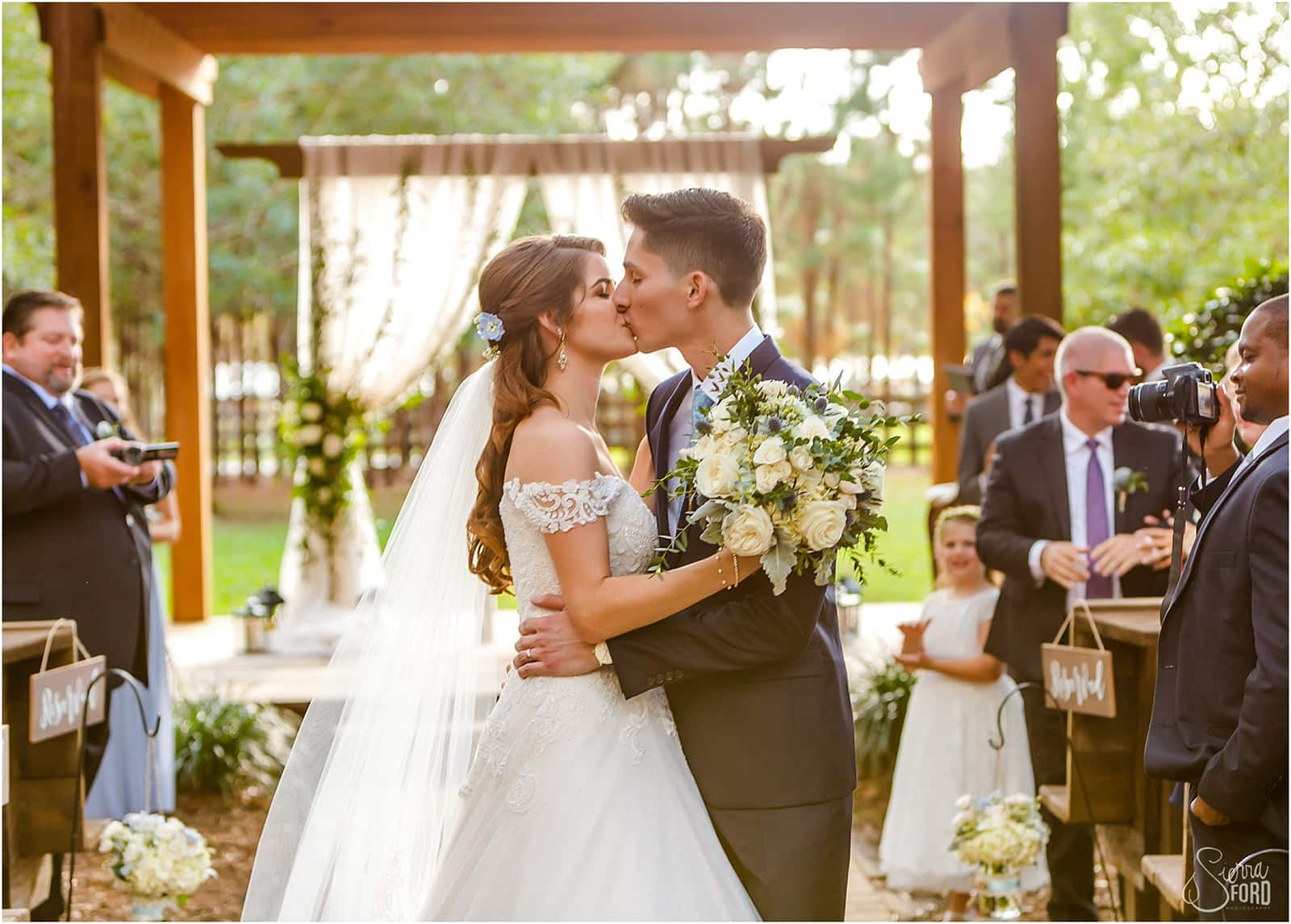 Amber and Phillip's kiss at outdoor wedding ceremony
