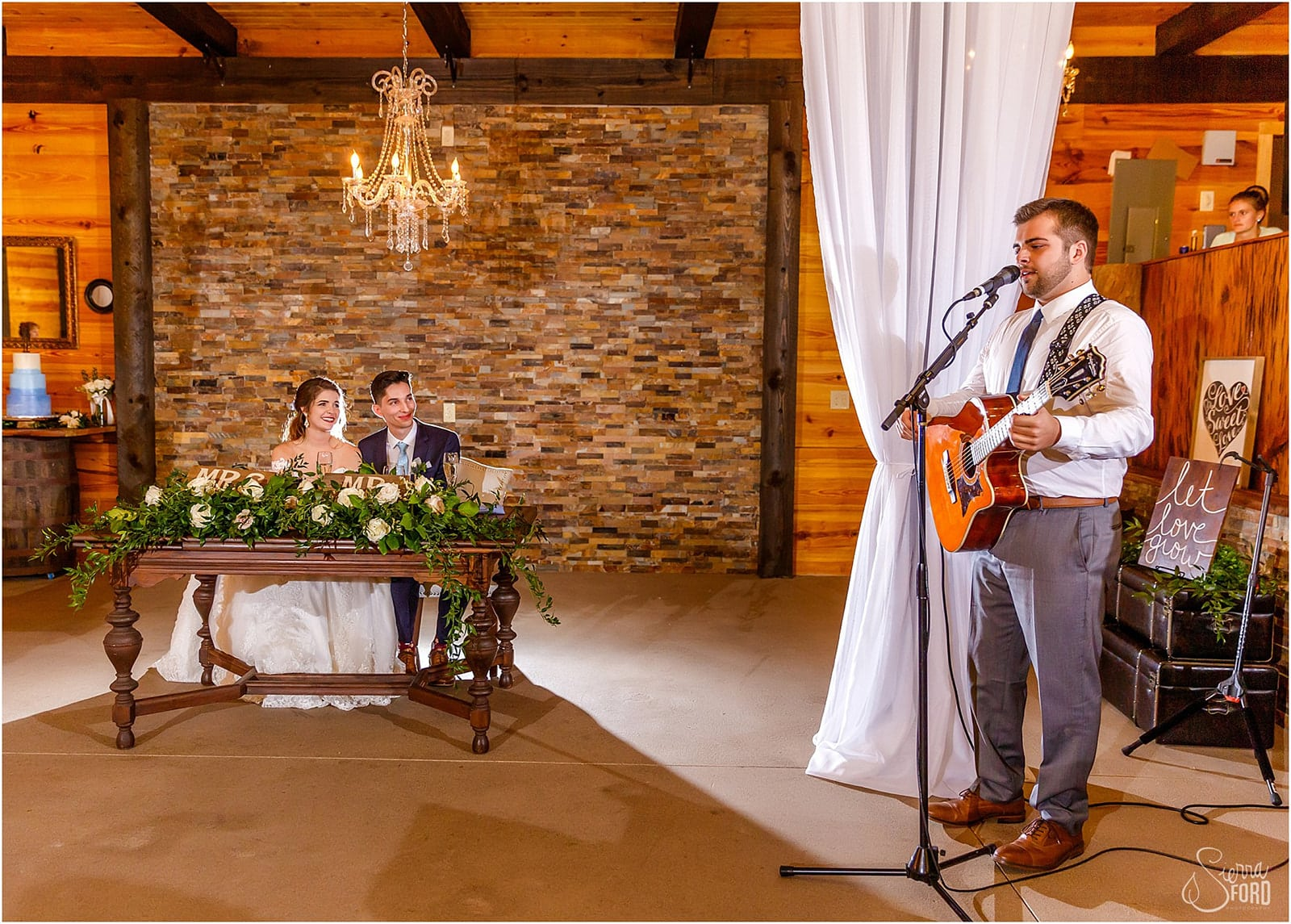 man singing song on guitar to newlyweds