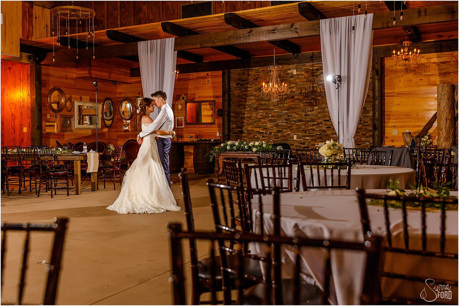 bride and groom dancing alone in reception hall