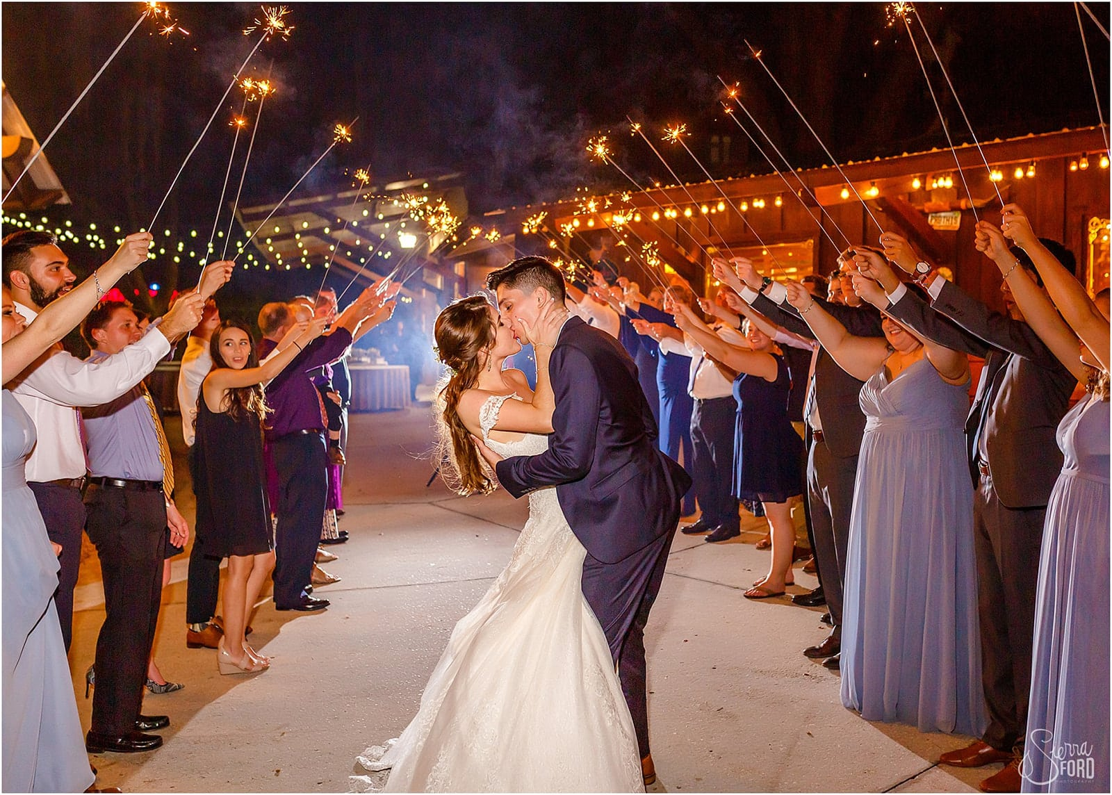 bride and groom kissing during sparkler exit
