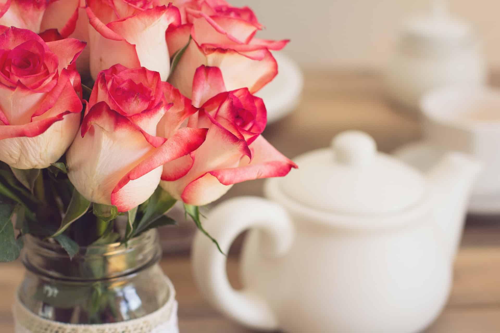 white teapot next to rose bouquet